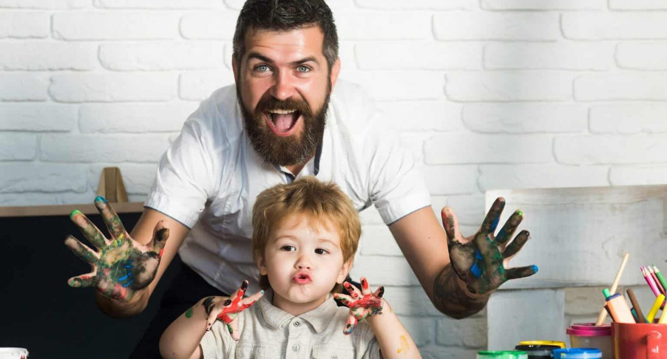 Joy family art, happy father and son show hands in bright colors, paint together picture, art for whole family, cheerful drawing teacher. Home education with parents. Happy childhood. Hands in paint